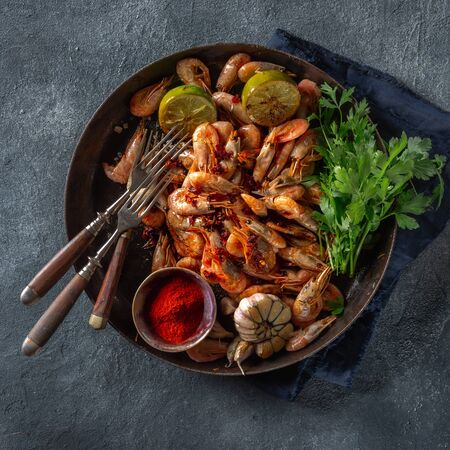 Fresh fried spiced shrimp in a frying pan on dark background top view