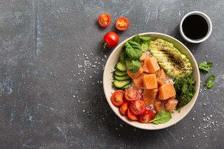 Organic poke bowl with salmon, avocado and vegetables on dark background