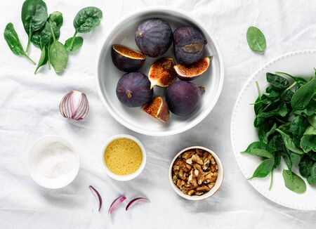 Fresh raw ingredients for cooking vegetarian salad of figs, nuts and spinach top view