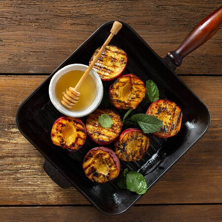 Peaches cooked in a pan grill top view summer food