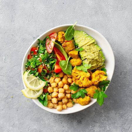 Bowl Buddha. Balanced healthy vegetarian food. Aloo gobi, tabouli salad, chickpeas, avocado, tomato and spinach. Top view. Free space for your text