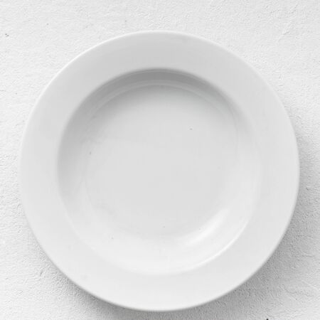 Empty white round plate on a white background top view 写真素材