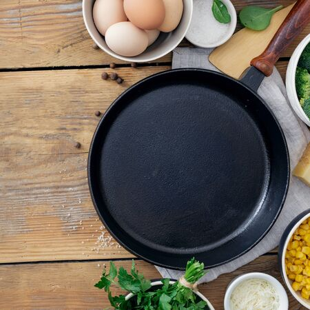 Healthy breakfast table with empty cooking pan and ingredient for cooking on wooden background top view copy space. Broccoli, eggs, spinach and cheese on table