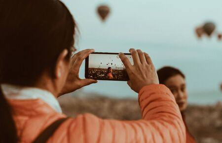 Woman taking a picture of a beautiful girlfriends with her smartphone against the Background of balloons in Cappadocia, Turkey