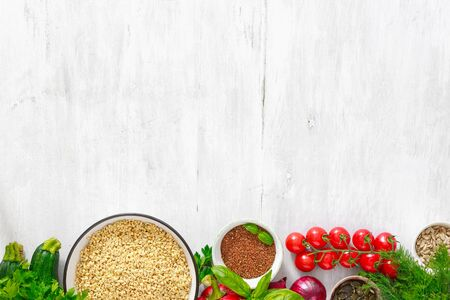 Ingredients for cooking diet and healthy food. green buckwheat, sunflower and flax seeds, vegetables and greens top view on wooden white background with copy space