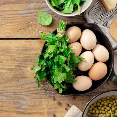 Healthy breakfast table with ingredient for cooking. peas, eggs, spinach, parsley and cheese on wooden background top view copy space