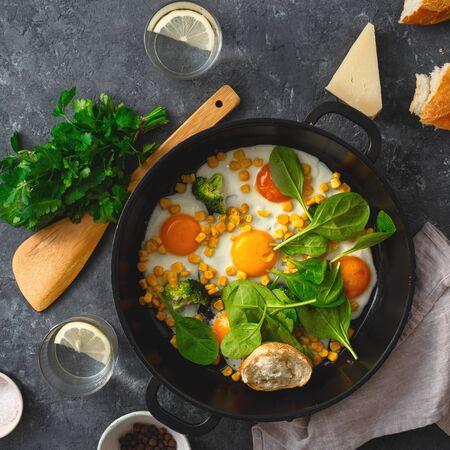 Breakfast fried eggs frying pan top view on dark stone background