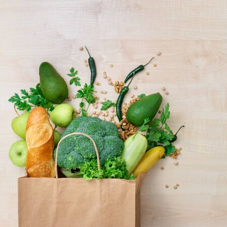 Groceries shopping bag with healthy food on a wooden background top view