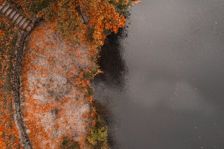 Autumn background. Aerial drone view of the lake and orange tree