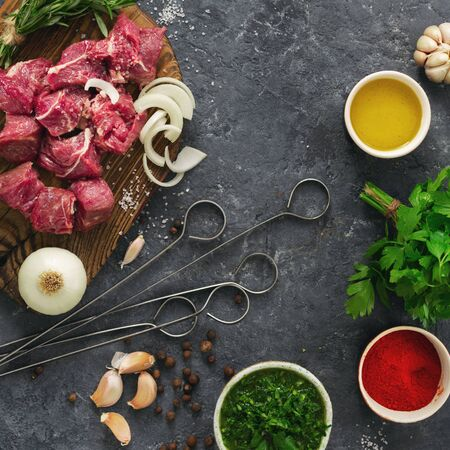 Ingredients for cooking meat with vegetables on a dark background top view. Preparation beef meat