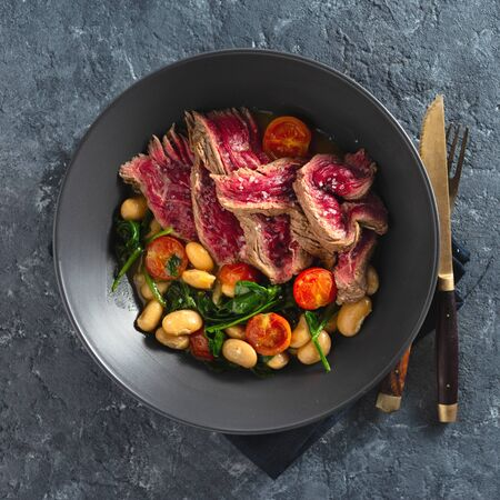 Dinner plate with beef steak with white beans, spinach and tomatoes on dark stone background top view with free co