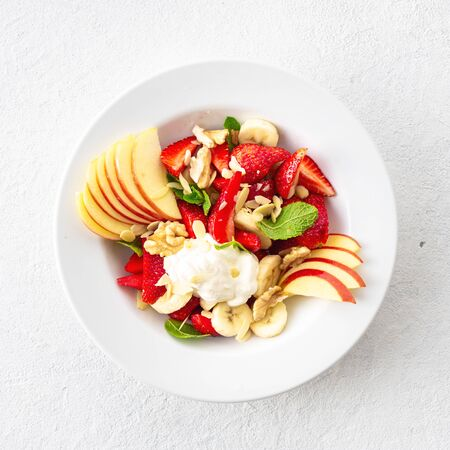 Fruit salad bowl on a white background top view. Healthy summer food