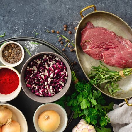 Raw beef meat with ingredients for cooking healthy food. Uncooked  beef meat with herbs, spices and beans top view 写真素材