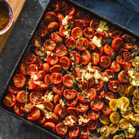Baked juicy cherry tomatoes into a baking tray on dark background top view