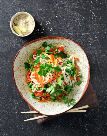 Thai noodles with vegetables on dark background top view