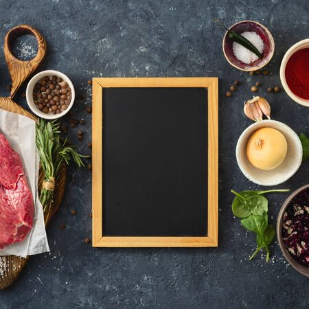 Cooking table with blank chalk board and beef meat, vegetables, spices, herbs top view. Food menu