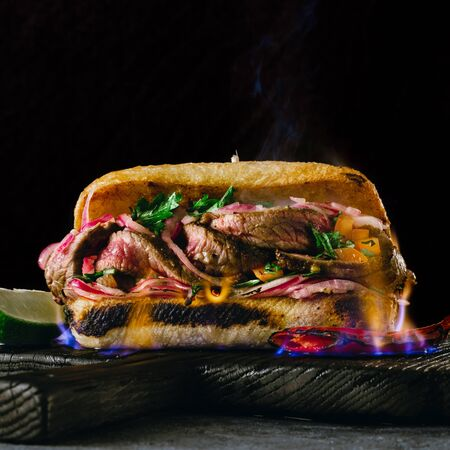 Grilled spicy steak sandwiches steak in fire flame on wooden cutting boards on dark background close up 스톡 콘텐츠
