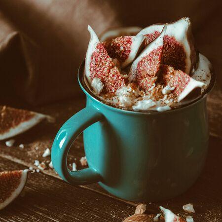 Vegetarian dessert from figs, almonds and vegan yogurt on dark wooden table. Rustic style