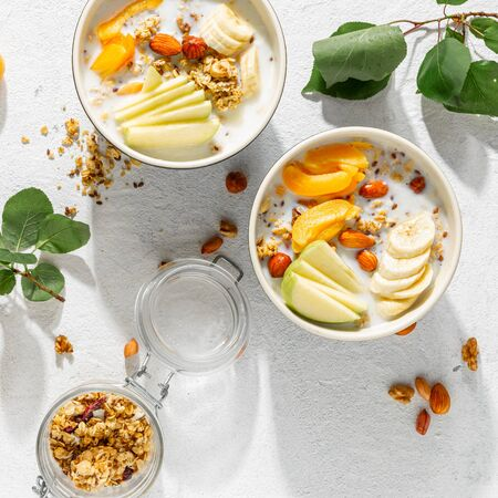 Granola cereal with fruits, nuts, milk and peanut butter in bowl on a white background. Healthy breakfast cereal top view  写真素材