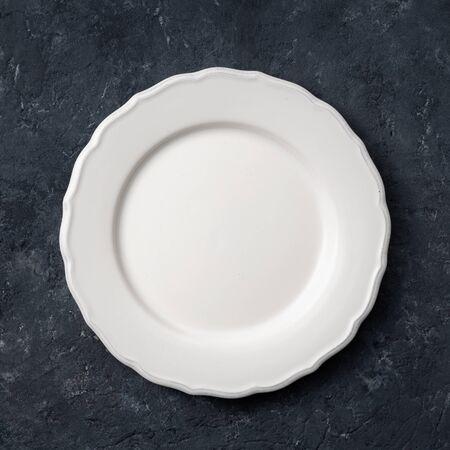 White vintage ceramic empty plate on dark stone background 写真素材