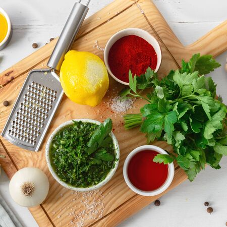 Top view cooking background. Raw ingredients for cooking green Chimichurri or Chimmichurri salsa or sauce on white wooden table 스톡 콘텐츠