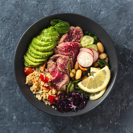 Healthy food buddha bowl with beef steak, beans, couscous, avocado and vegetables on dark background with copy space Stockfoto