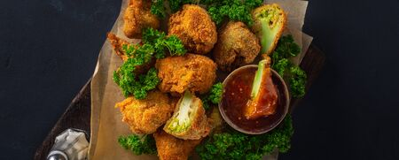 Vegan Buffalo wings made from roasted broccoli top view. Tasty vegetarian food top view