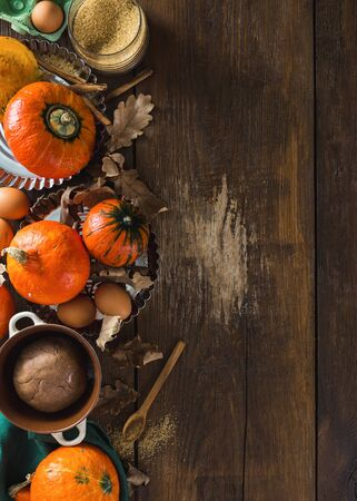 Raw ingredients for cooking pumpkin pie with dry autumn leaves on wooden background with copy space Stok Fotoğraf