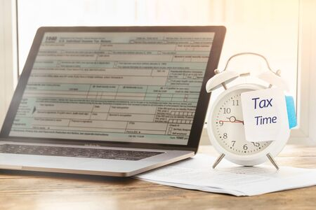 Tax Time Concept. Alarm clock with note reminder of the need to file tax returns, tax form Stock Photo