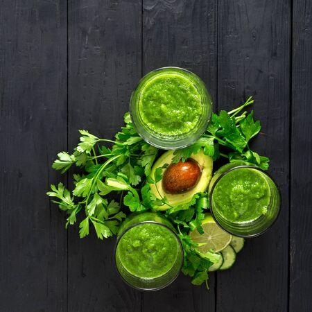 Green detox smoothie on a dark wooden background top view