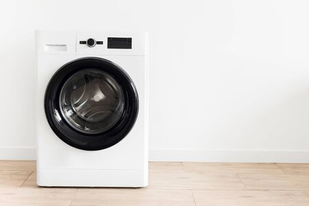 White laundry room with a washing machine Copy space