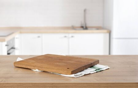 kitchen cutting board on the kitchen table top on blur kitchen background with place for montage product display Stock Photo - 142950467