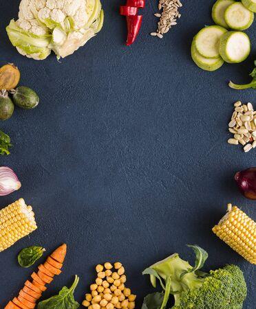 World vegan day. Frame of Fresh vegetarian ingredients for cooking vegan plate on dark background overhead view