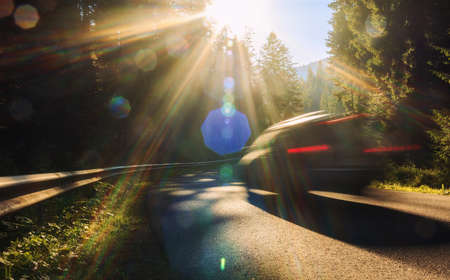Blurred car in motion is driving on mountain road in the autumn forest at sunset. Travel by car concept background