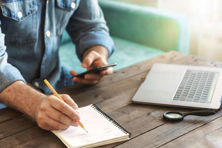 Business Freelancer man working at home with smartphone and laptop. Ð¡lose up man hand writing in notebook on wooden table. Remote work concept