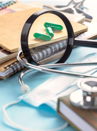 Doctor's table with magnifying glass, capsules, stethoscope or phonendoscope, notebooks and documents