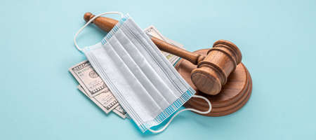 Judge gavel with medical mask and money on blue background. Corruption in the medical field concept
