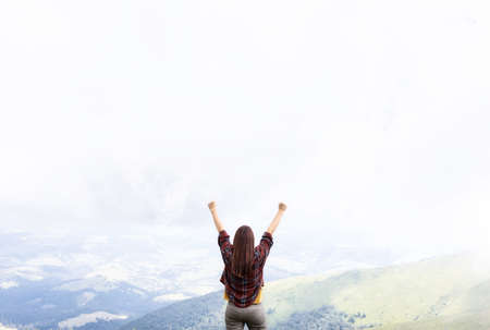 Freedom concept. Woman with hands up standing on top of mountain enjoying the view