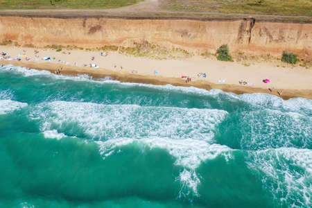 Sand beach with turquoise water. Aerial view of people on the beach. Vacation travel and relax concept