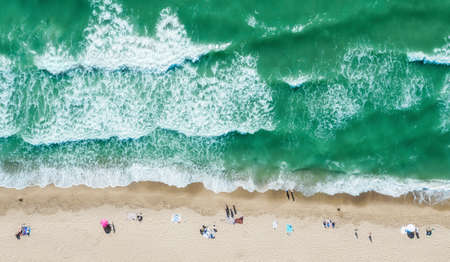 Aerial view of people on the beach. Sand beach with turquoise water. Vacation travel and relax concept