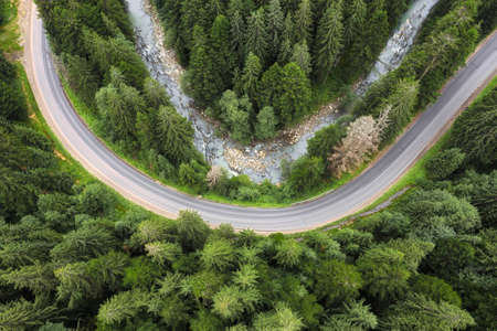 Winding asphalt mountain road road with river through the green pine forest