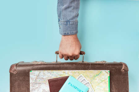 Male hand holds retro suitcase with map and passport with money on blue background minimal creative travel concept