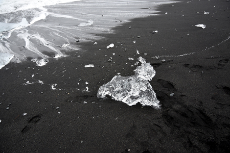 ice sculpture: A natural animal ice sculpture on a beach near Jokulsarlon volcano in Iceland. The crystal clear ice looks great against the black volcano sand. It Seems almost as if the sculpture is crawling from the sea onto the beach. Stock Photo