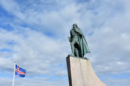 A statue of explorer Leif Eriksson in front of the church Hallgrimskirkja in Reykjavik, Iceland. Next to it the Icelandic national flag. Stock Photo