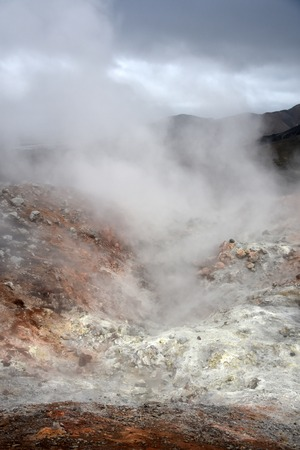 barely: Landmannalaugar in the south east of Iceland. The landscape is a geothermal wonderland-including sulfur lava steam coming out of the multicolored rhyolite mountains, so thick, you can barely see anything. Stock Photo