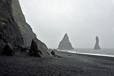 mystique: Black beach at Dyrholaey, Iceland in rainy weather with big black rocks in the sea. The rain give a mystery charm to the volcanic beach landscape. The one, almost relieved, person walks on the beach alone. Stock Photo