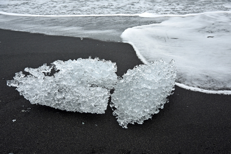 ice sculpture: A black volcano beach near Jokulsarlon in Iceland with ice sculpture like crystal rocks lying on the beach and in the sea. Stock Photo