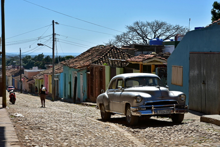 A beautiful, silver old-timer in a colorful street in Trinidad, Cuba. The car does not seem to fit into the environment and stands out nicely.