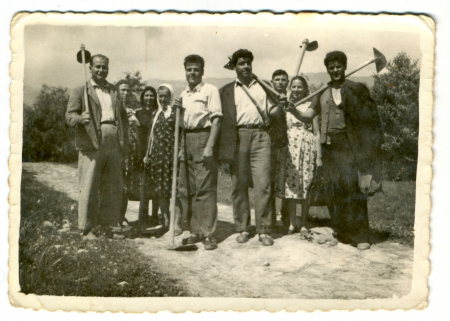 historical clothing: Villagers posing with agricultural machinery - circa 1945