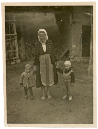 Two children and grandmother standing in the yard - circa 1945  photo
